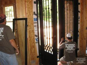 Scardino Doors team installing locks and hardware on a custom wrought iron door